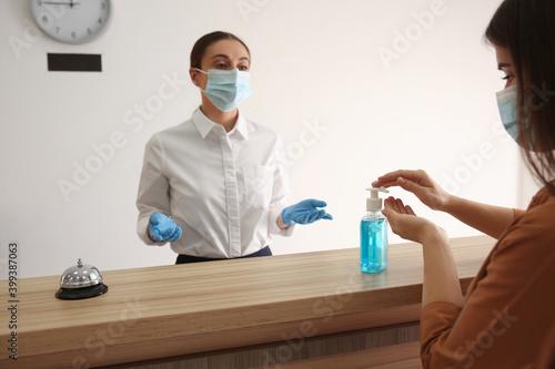 Canvas-taulu Woman applying antiseptic gel at hotel reception, closeup