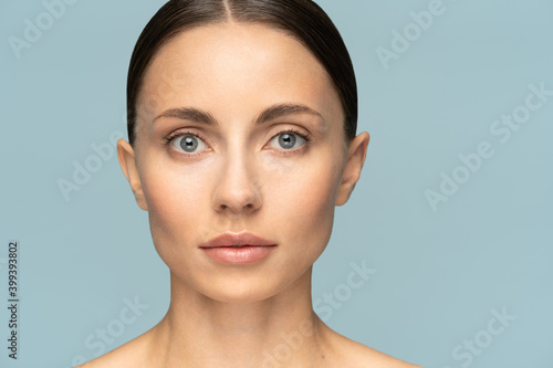 Fotografie, Obraz Close up of woman face with perfect fresh clean skin without make up and wrinkles, looking at camera over studio blue background