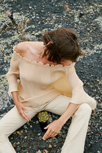 Girl In Beige Clothes Sitting On The Rocks And Having Green Flower In The Middle Of Her Legs