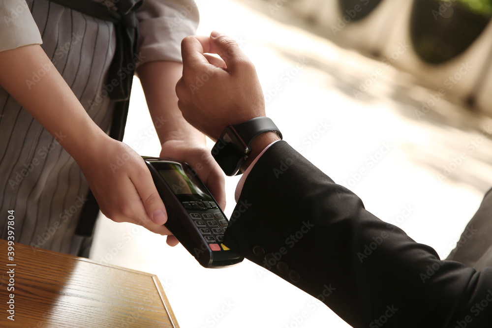 Fototapeta Man making payment with smart watch outdoors, closeup