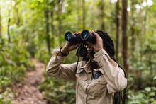 Girl Looking Through Binoculars In The Jungle