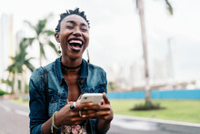 Afro Woman Laughing Using Smartphone