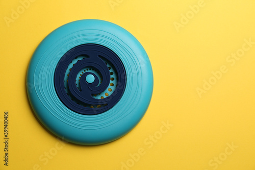 Photo Blue plastic frisbee disk on yellow background, top view