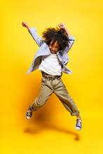 Black Kid Jumping In Studio Smiling.