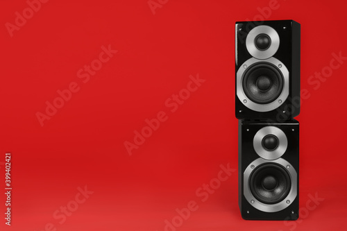 Canvas Print Modern powerful audio speakers on red background, space for text