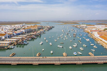 Aerial View Of A Harbor With The Boats Docked And A Bridge Over The Rio Carrera Connecting The Island Of Isla Cristina, Huelva, Spain.