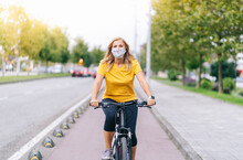 Woman Wearing Protective Face Mask Cycling On Bicycle Lane In City
