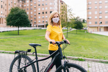 Mature Woman Wearing Protective Face Mask Standing With Bicycle On Footpath In City During COVID-19
