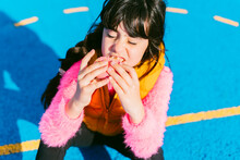 Cute Girl Eating Donut While Sitting On Basketball Court