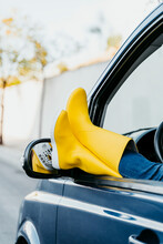 Carefree Woman Relaxing With Legs On Car Window During Road Trip