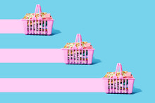 Studio Shot Of Three Pink Shopping Baskets Filled With Clothing Leaving Pink Trails
