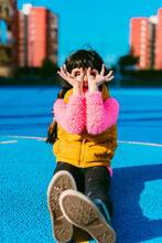 Girl Forming Binoculars With Fingers While Sitting On Sports Court During Sunny Day