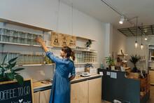 Female Owner Arranging Glass Jars On Shelf In Cafe