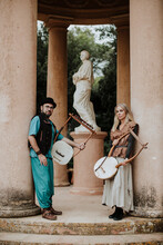Male And Female Couple Holding Lyra Musical Instrument By Pillar