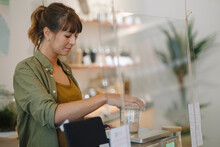 Businesswoman Weighing Grain Jar On Weight Scale In Cafe