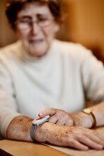 Wrinkled Worried Woman Pressing Emergency Button On Wrist Over Table At Home