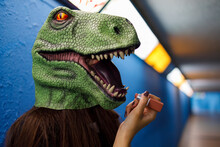 Woman Applying Lipstick While Wearing Dinosaur Mask Against Blue Wall
