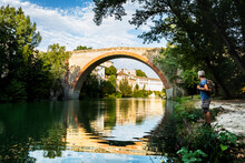Man Standing And Looking At Ancient Ponte Della Concordia Bridge At Fossombrone, Marche, Italy