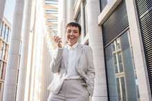 Happy Businesswoman Holding Smart Phone While Standing Against Modern Office Building