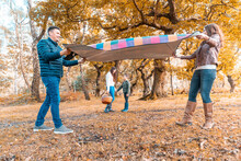 Parents Laying Down Picnic Blanket While Children Standing Behind In Park During Autumn