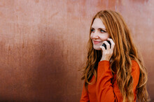 Smiling Woman Talking On Mobile Phone By Brown Wall