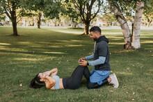 Man Helping Woman Doing Sit Ups While Sitting On Grass At Backyard