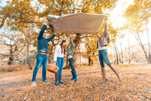 Son Jumping Under Picnic Blanket While Parents Laying Down In Park During Autumn