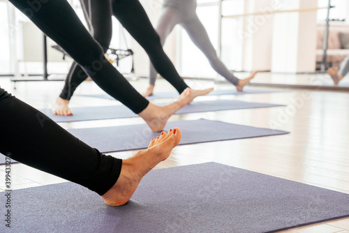 Tablou Canvas Cropped view of girls exercising yoga doing feet and legs stretching standing in