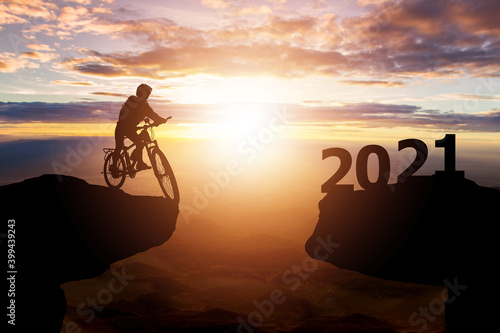Fototapeta Success 2021 new year concept. Silhouette of cyclist riding between 2020 years with sunset background obraz