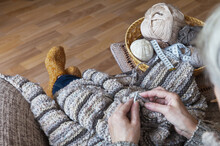 A Woman Is Knitting A Warm Woolen Striped Sweater While Sitting In A Comfortable Armchair At Home. Hobby And Needlework Concept. Focus On Knitted Fabric, Hands And Legs Out Of Focus