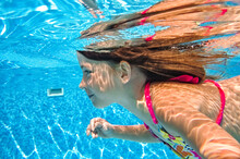 Little Child Swims Underwater In Swimming Pool, Happy Active Baby Girl Dives And Has Fun Under Water, Kid Fitness And Sport