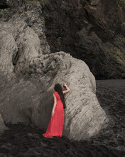 Girl In Red Dress Leaning Against Black Lava Rock Wall In Vik, Iceland