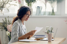 Important Message. Focused Attentive Young Woman Florist Designer Sitting At Work Desk In Office Studio. Small Business Owner Involved In Reading Paper Letter From Bank Of Credit Loan Terms Conditions