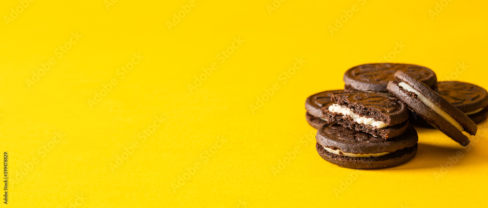 Fototapeta Broken Chocolate sandwich cookies with vanilla cream filling  and  cookies crumbs on yellow background.Large image for banner