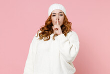 Secret Young Redhead Plus Size Body Positive Woman 20s In Warm White Sweater Hat Saying Hush Be Quiet With Finger On Lips Shhh Gesture Looking Camera Isolated On Pink Color Background Studio Portrait.