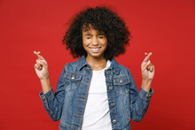 Funny Little African American Kid Girl 12-13 Years Old In Denim Jacket Wait For Special Moment Keeping Fingers Crossed Eyes Closed Making Wish Isolated On Red Background. Childhood Lifestyle Concept.