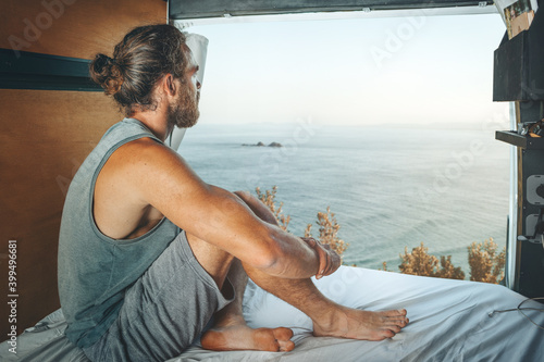 Foto Man sitting in the back of a camper van looking at the sea