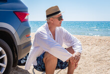 A Man Wearing A Sun Hat Relaxes Against The Blue Sea And Enjoys The Scenic View. Summer Vacation At The Sea.