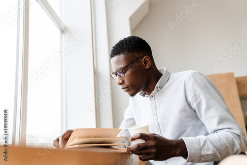 Fototapeta Afro american focused man reading book and drinking coffee