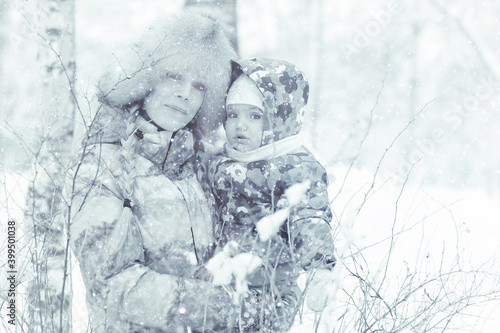 Fototapeta small child and young mother in the winter outside in warm clothes fun obraz
