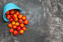 Overhead View Of Fresh Cherries Poured Out Of The Blue Basket On Gray Background