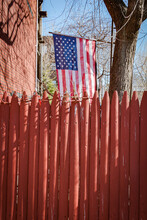 A Portrait Format Vertical Photo Of An American Flag Hanging In A Backyard Behind A Red Painted Fence In The Morning Sun, Showing Pride And Patriotism.