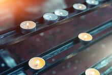 Many Small Burning Votive Prayer Candles Burning On Rack Altar In Church Or Temple In Europe. Saint Religious Holidays Holy Candlelight Celebration Background. Catholic Christian Christmas Flame