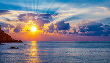 Calm Sea And Cloudy Sky Pierced With Sun Rays. Beautiful Nature Background.