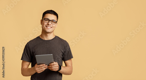 Cheerful young attractive man in glasses looks at camera, holds digital tablet on online lesson