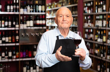 Confident Elderly Male Winemaker Inviting To Wine House, Offering Glass Of Wine For Tasting. High Quality Photo