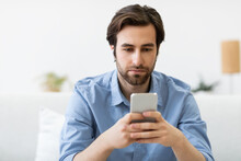 Serious Man Using Smartphone Wearing Earbuds Sitting On Sofa Indoors
