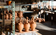 Clay Jugs And Utensils On Racks In Store. High Quality Photo