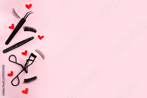 Fototapeta Lash curler, false lashes and tweezers for eye make-up on pink background with r