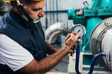 Industrial Worker Checking Pressure Gauge